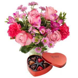 Bukett med blommor i rosa och cerise; rosor, nejlikor, germini +en ask med chokladhjärtan. Gåvan finns att köpa hos Euroflorist.