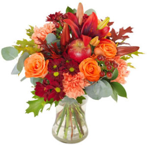 Bukett med blandade blommor i orange och rött +dekorationsäpple. Skicka blommorna med bud från Euroflorist och överraska till Halloween!