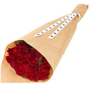 Bukett med röda rosor. Omslagspapper runt buketten. Blommorna ingår i Euroflorists utbud av Alla hjärtans Dag-rosor.