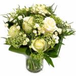 Bukett från Euroflorist med vita rosor och småblommigt vitt tillsammans med gröna blad.
