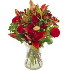 Bukett med röda liljor, röda rosor och röda bär. Ur Euroflorists utbud av blombuketter.