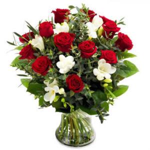 Bukett med röda rosor, vit freesia och gröna blad. Ur Euroflorists bukettsortiment för blomsterbud till utlandet.