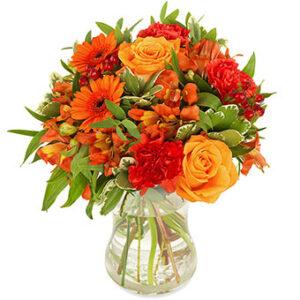 Rundbunden bukett med blandade orange blommor, bl a rosor. Ur Euroflorists bukettsortiment.